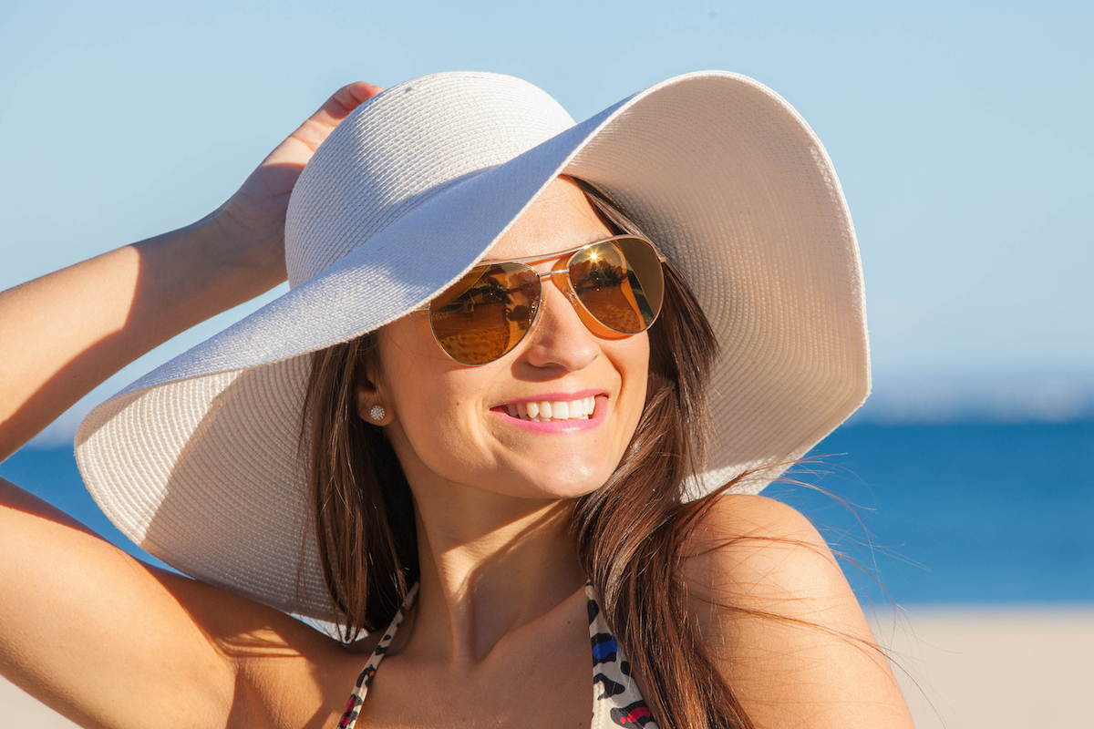10f43c04a0 smiling woman on vacation with sun hat and glasses.